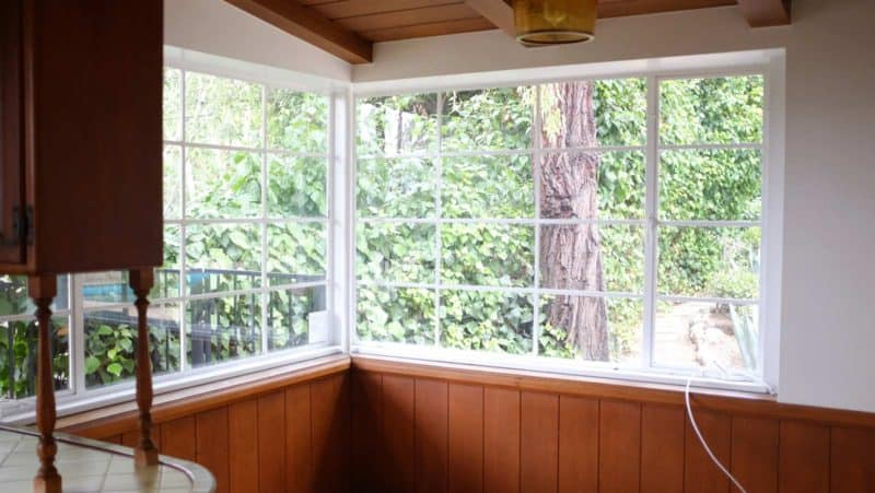 A corner of a room with a large windows.