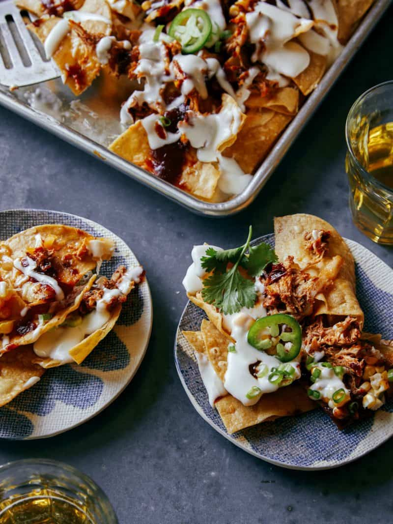 Chipotle chicken nachos served on blue plates next to tray.