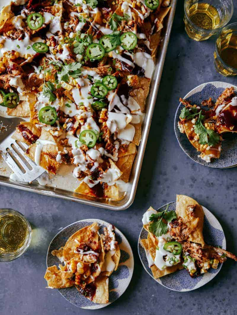 A sheet pan of chipotle chicken nachos with servings on small plates.