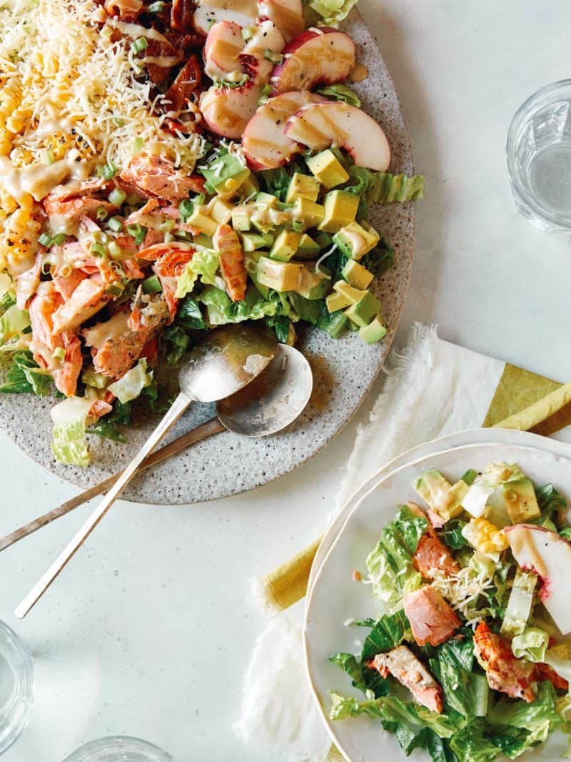Salmon summer salads served on plates with spoons.
