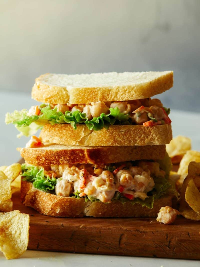 Stacked chickpea salad sandwiches  with potato chips.