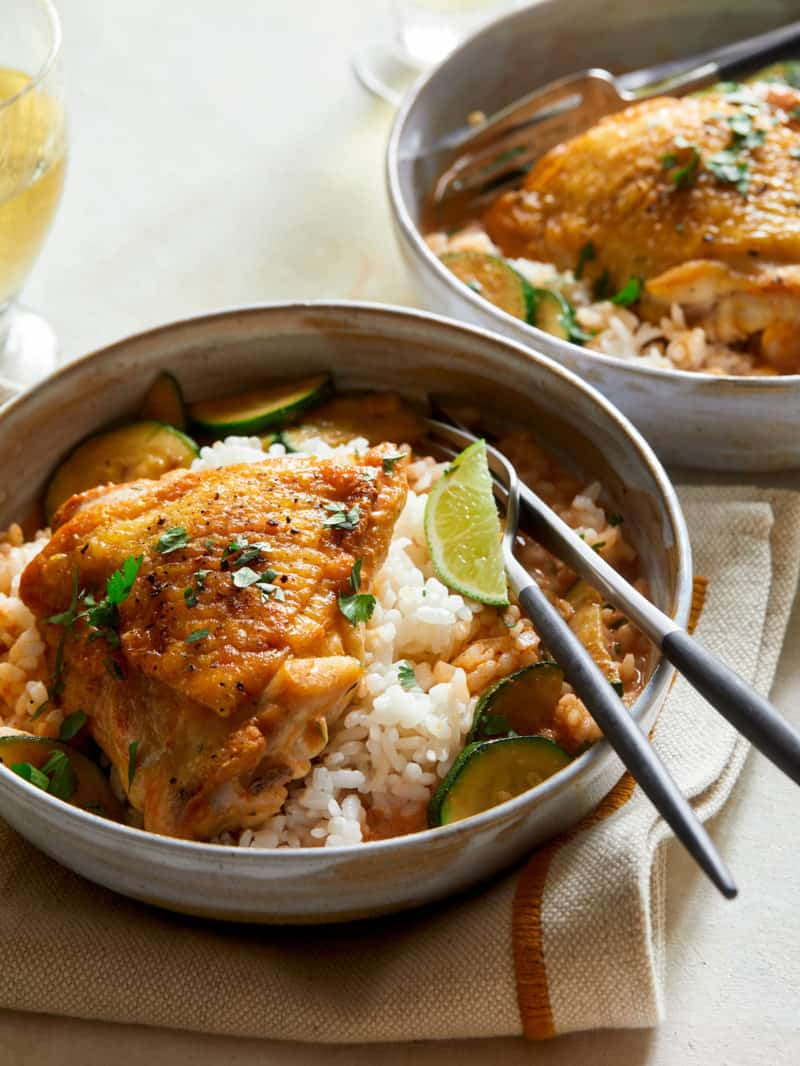 A close up of Thai red curry chicken thighs over white rice with a fork.