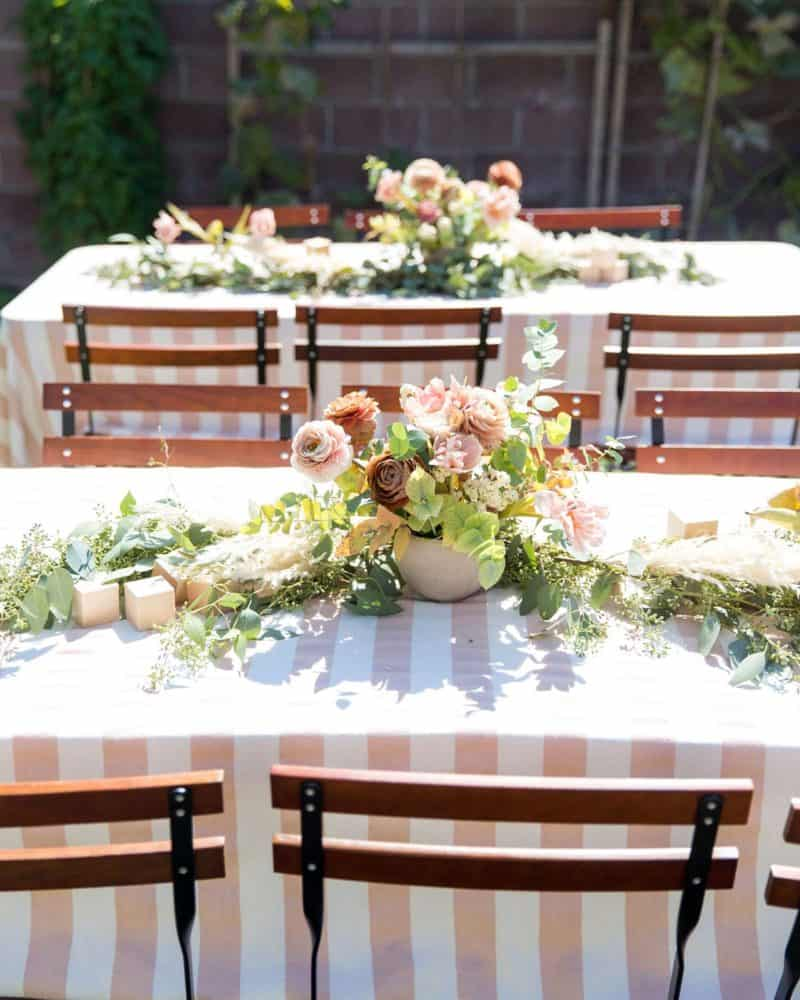 Party tables set with floral arrangement and decorative blocks.