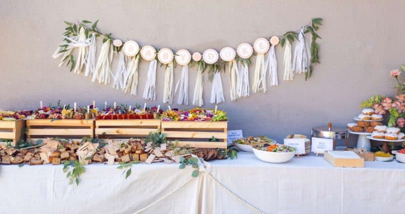 Table with charcuterie and cheese boards, salads, and a garland backdrop.