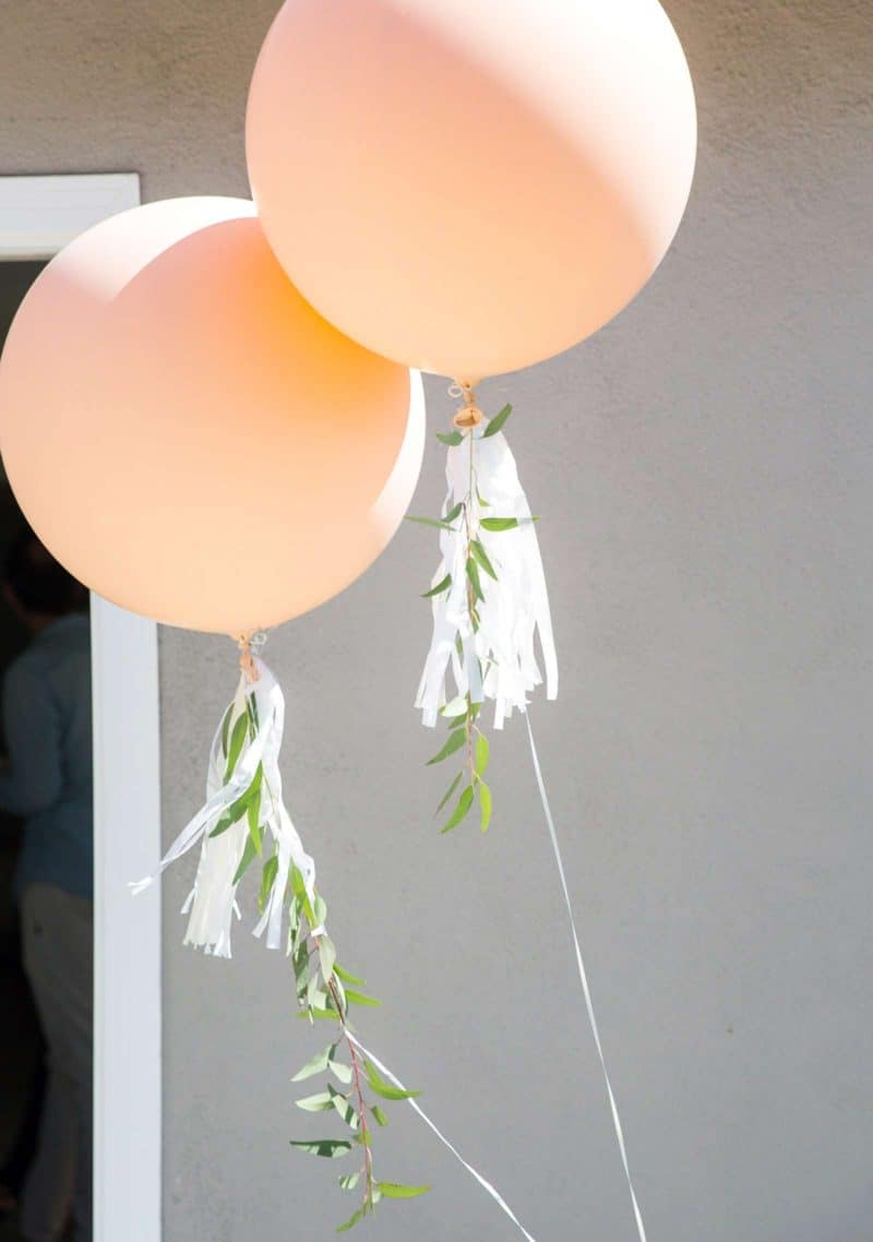 Two oversized balloons with hassle and greenery garland.