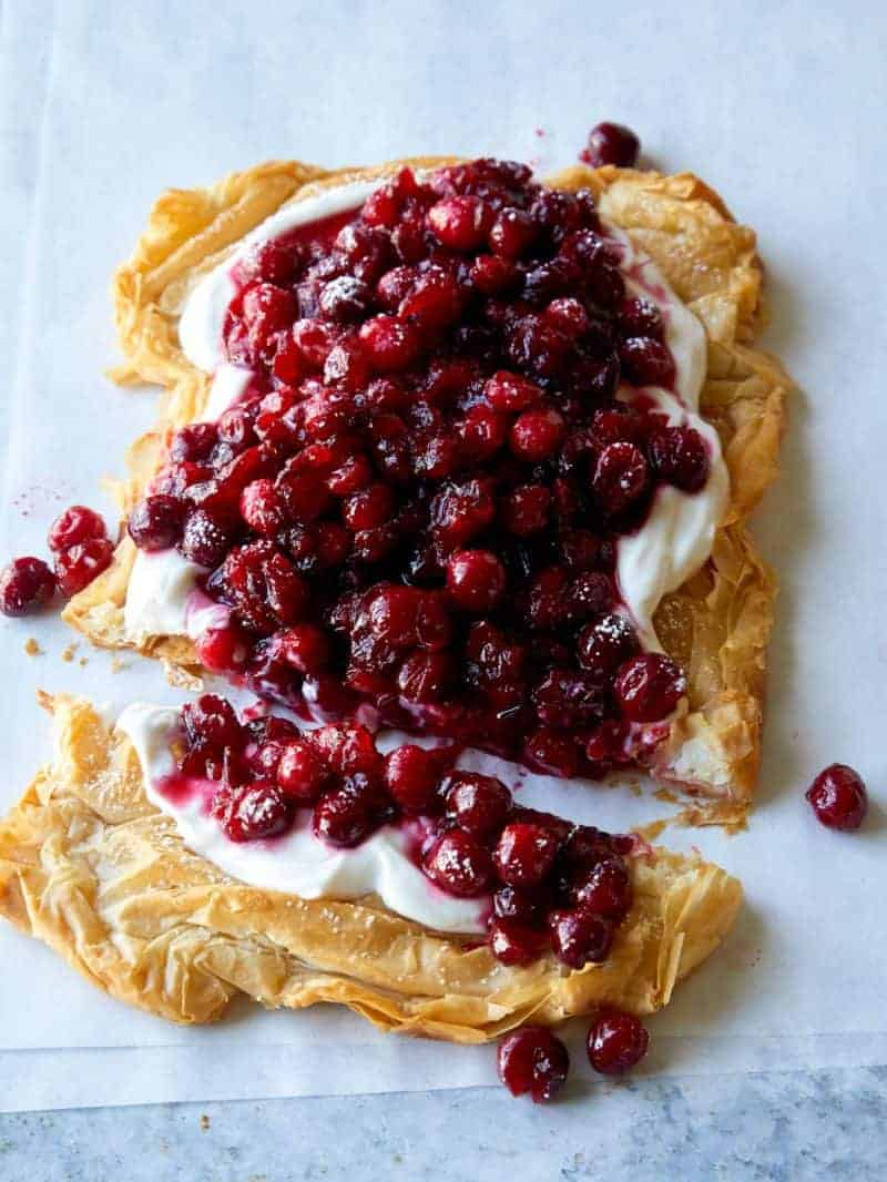 A crostata topped with yogurt filling and cranberries with the end cut off.