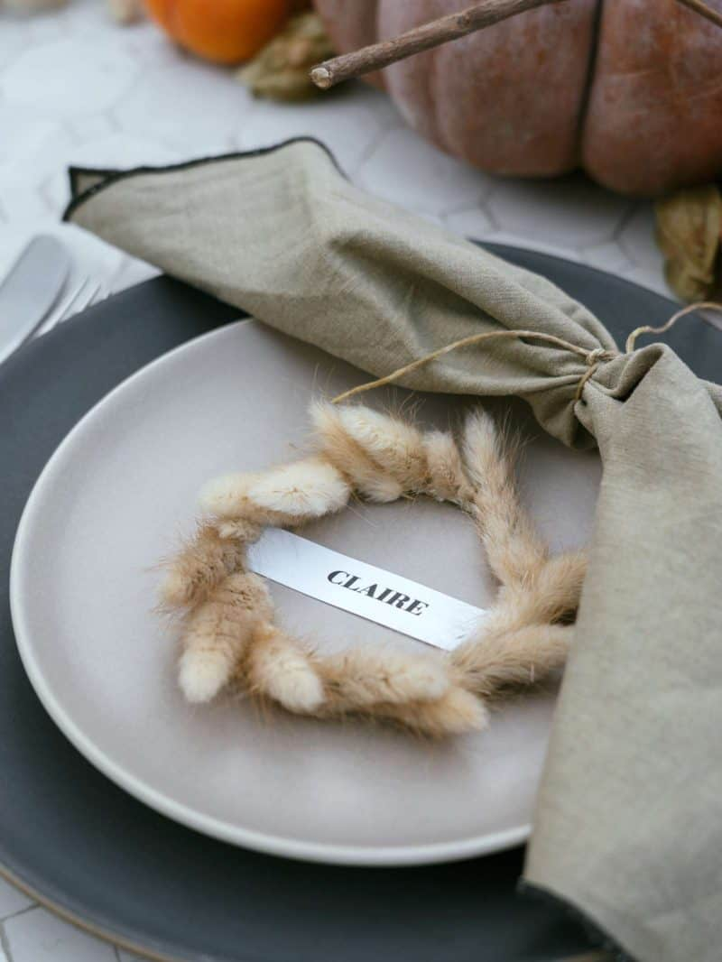 A place setting with a plate, mini wreath place card, and a napkin.