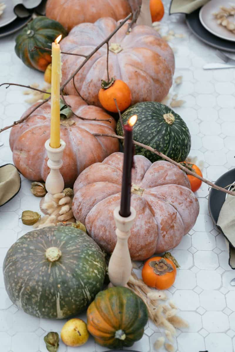 A close up of winter squash, fruits, dried bunny tails, and candles.