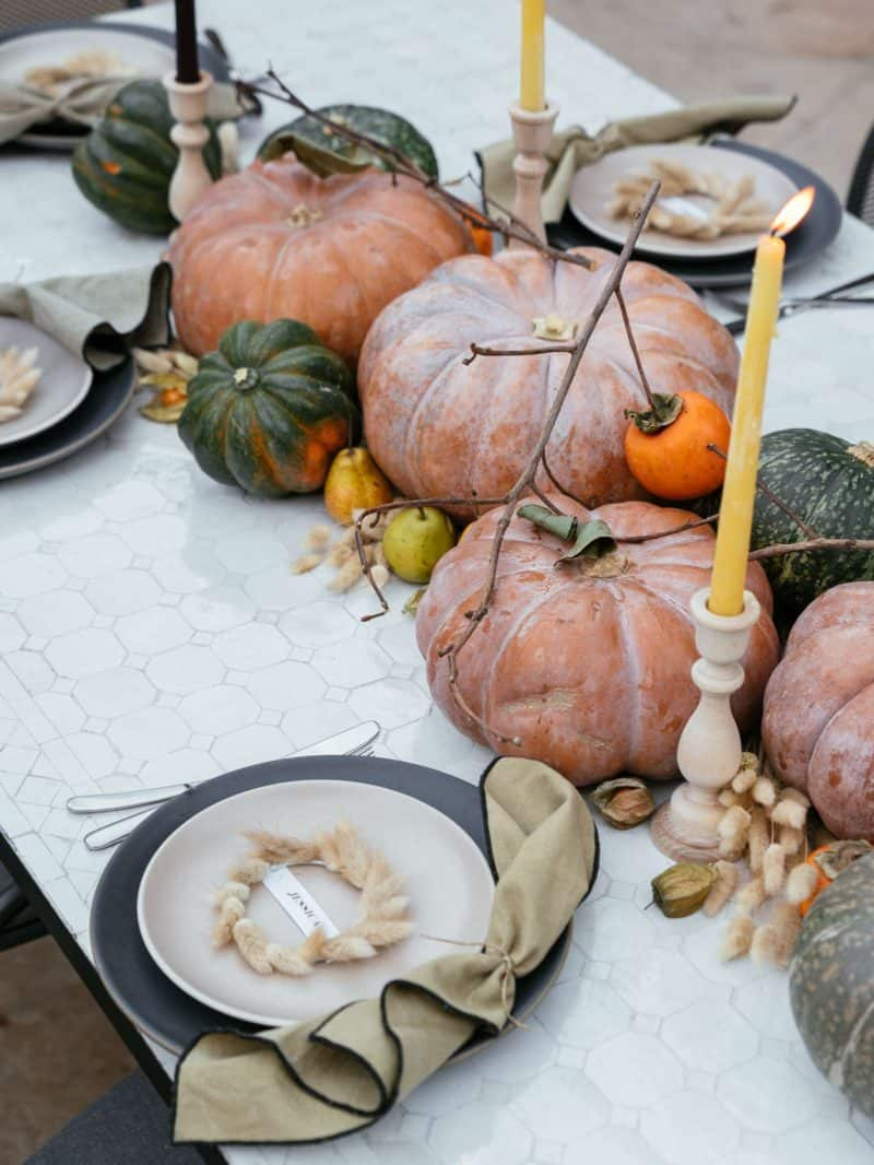 Place settings, winter squash, fruits, dried bunny tails, and candles in center.