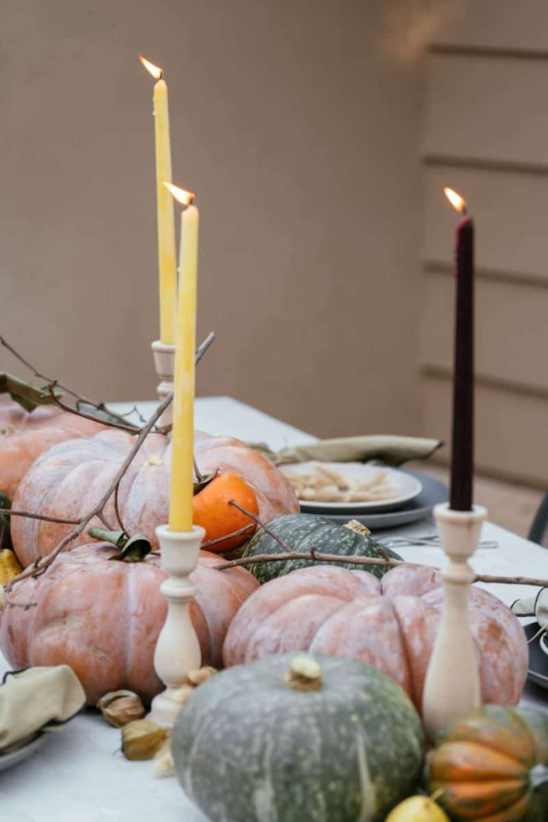 A close up of place settings, winter squash, fruits, and candles.