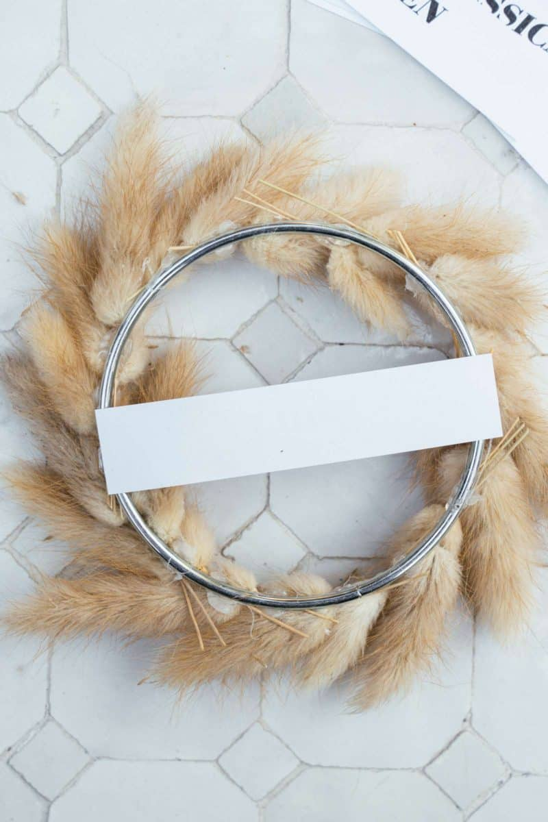 A close up of the back of a dried bunny tail wreath with paper label.