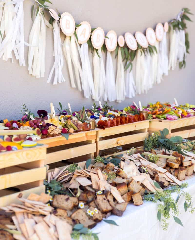 A close up of table with charcuterie and cheese boards, salads, and a garland backdrop.