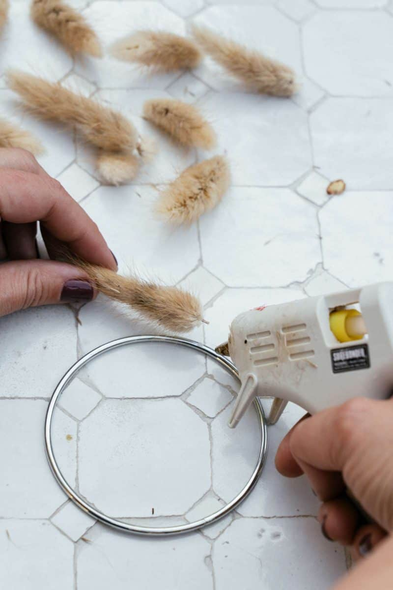 Dried bunny tails being hot glued to a ring.