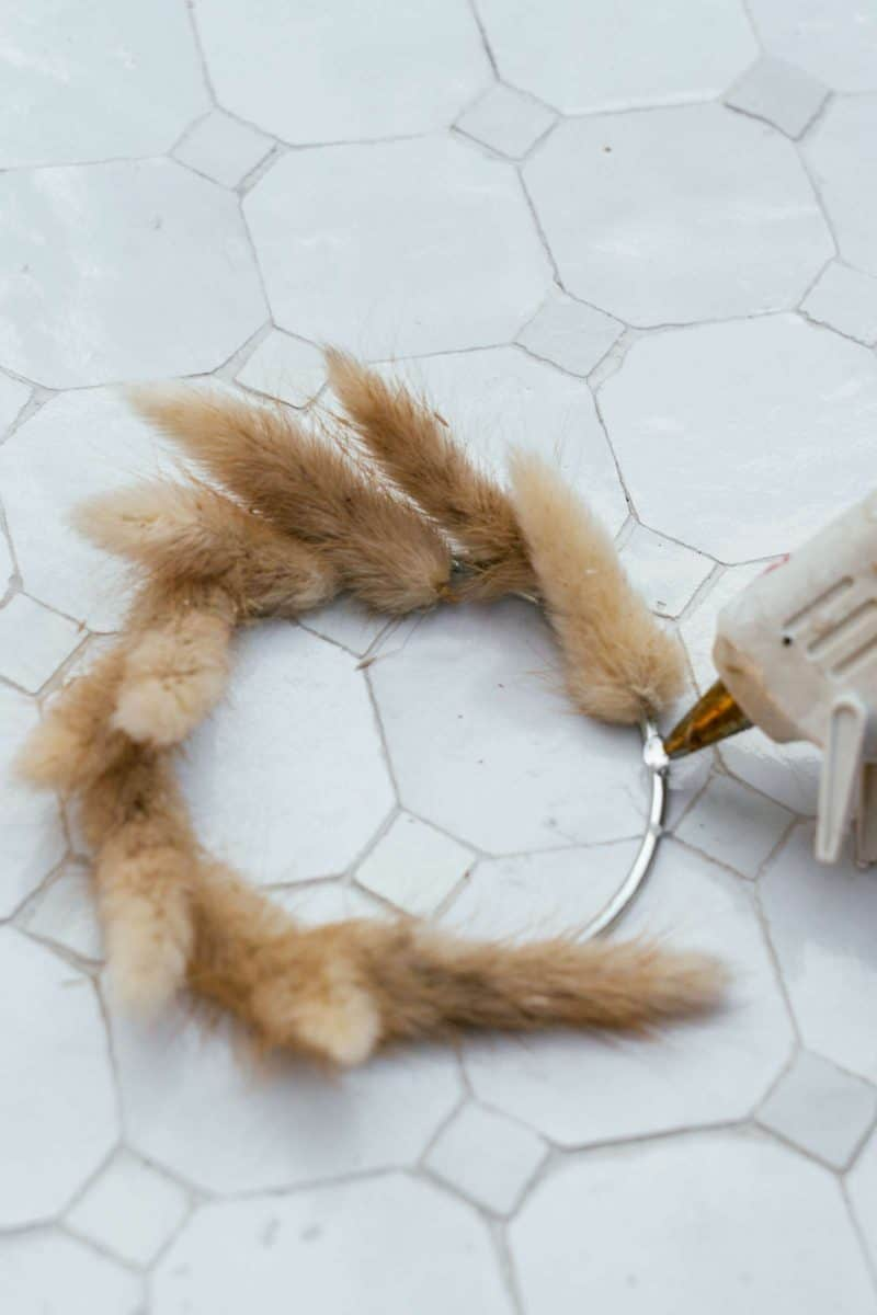 A close up of dried bunny tails being hot glued to a ring.