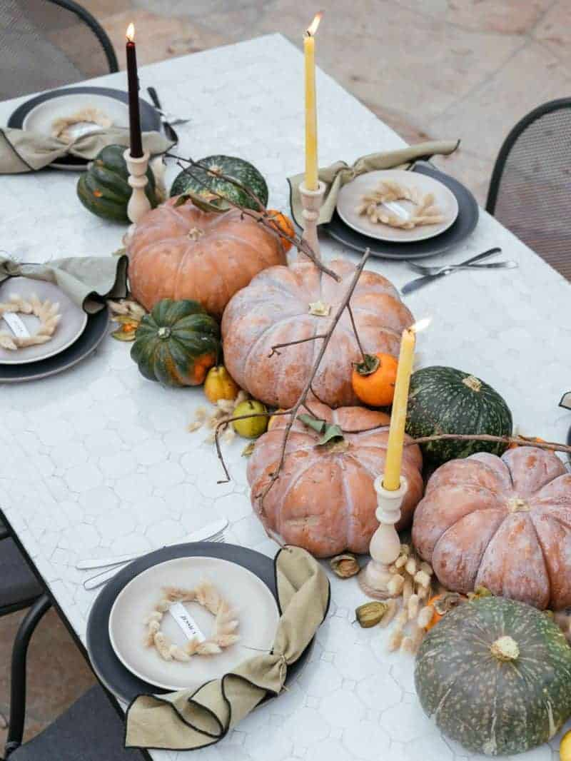 A table with place settings, winter squash, fruits, dried bunny tails, and candles in center.