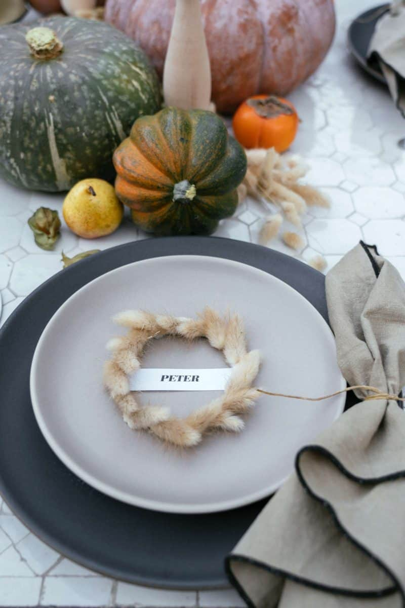 A place setting with a plate, mini wreath place card, and a napkin with table decor.