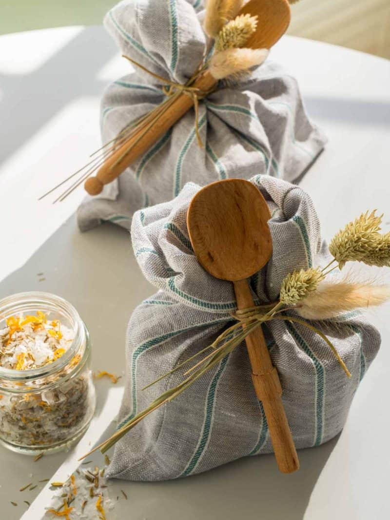 Reusable produce bags tied with dried grass and a wooden spoon.