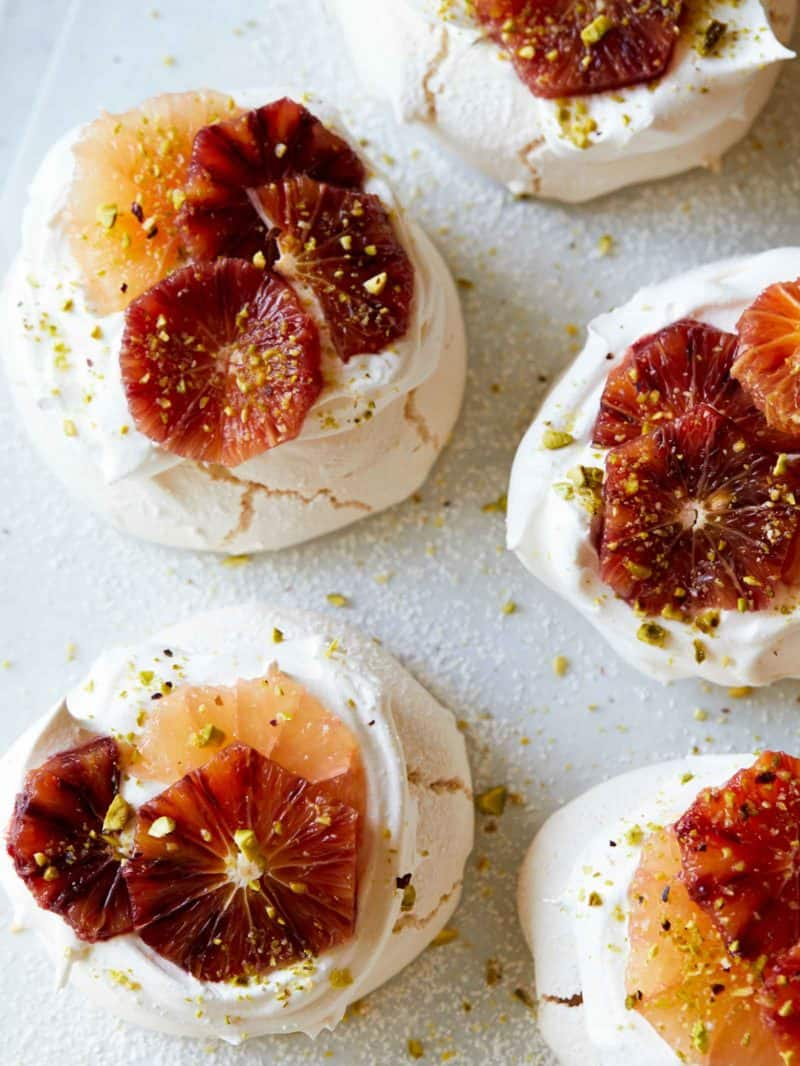 A close up of mini pavlovas with citrus on top.