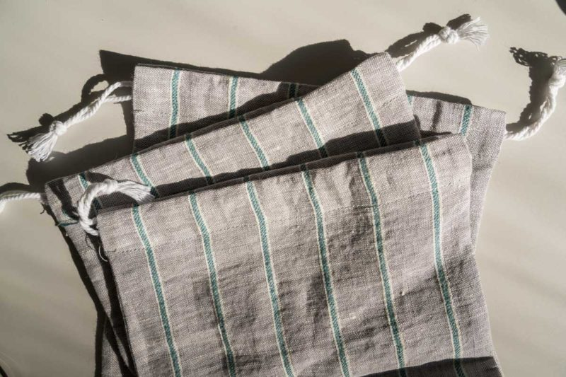 Close up of gray and green striped reusable produce bags.