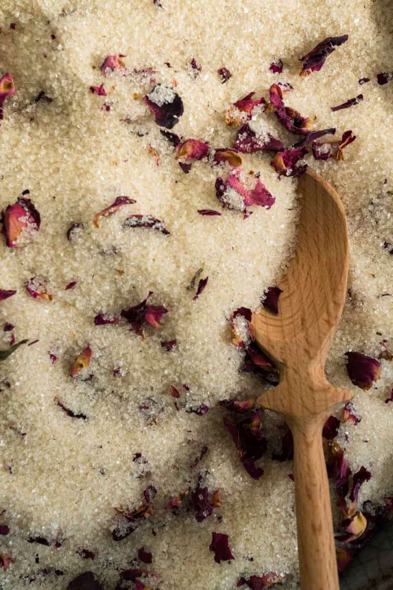 A close up of vanilla rose sugar with a wooden spoon.