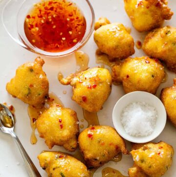 Hush puppies with sauce, salt, and spoon.