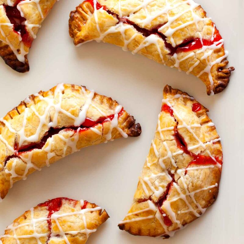 A close up of several cherry hand pies with cherry icing drizzle.