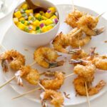 Coconut Shrimp skewers on a plate with mango salsa