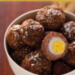 A recipe for mini scotch eggs in a bowl with one cut open.