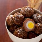 Hard boiled quail egg wrapped in sausage, coated in bread crumbs, then fried.