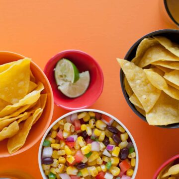 A bowl of grilled corn salsa next to bowls of tortilla chips and lime wedges.