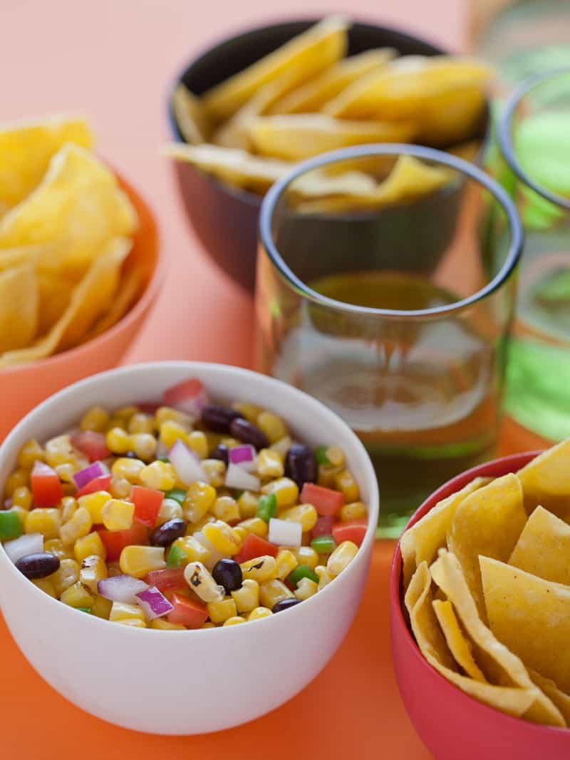 A close up of a bowl of grilled corn salsa next to bowls of tortilla chips.