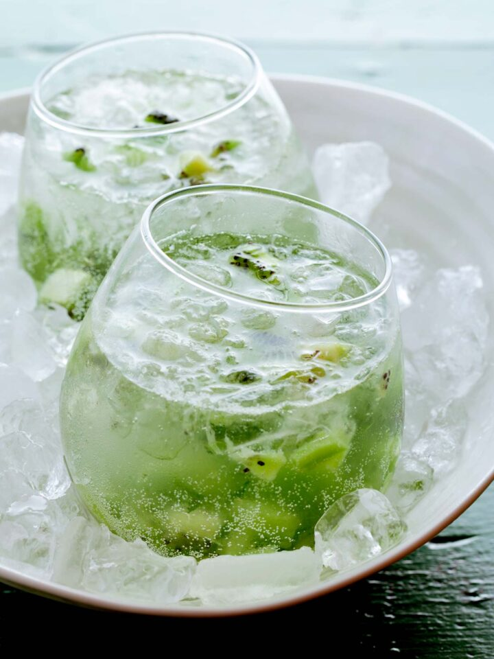 A close up of kiwi caipiroskas in a bowl of ice.