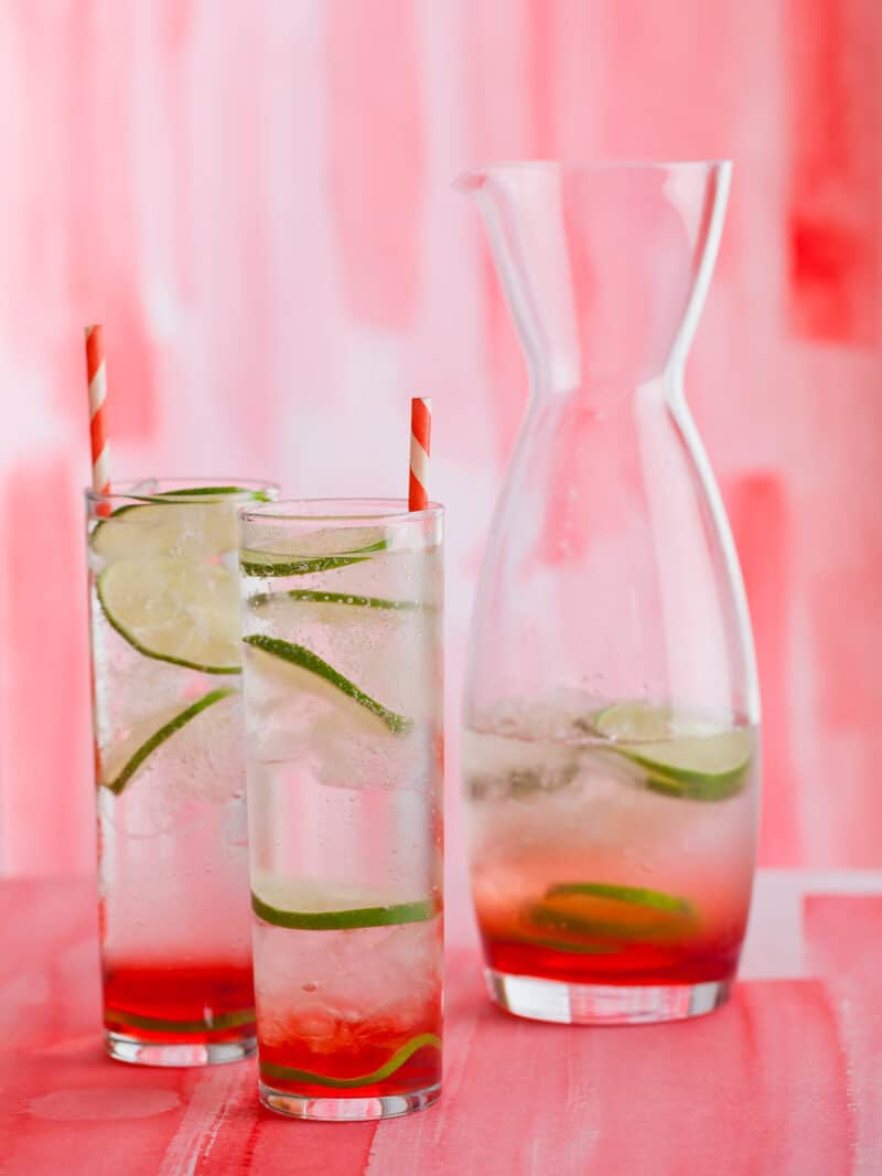 Sweet cherry gin and tonics with lime wheels and straws next to a half full carafe.