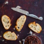 Crostini with a knife and a bowl of boozy bacon jam.