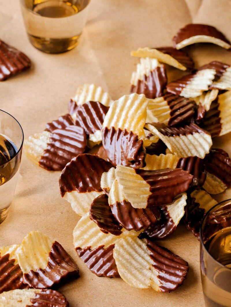 A table topped with chocolate covered potato chips with drinks.