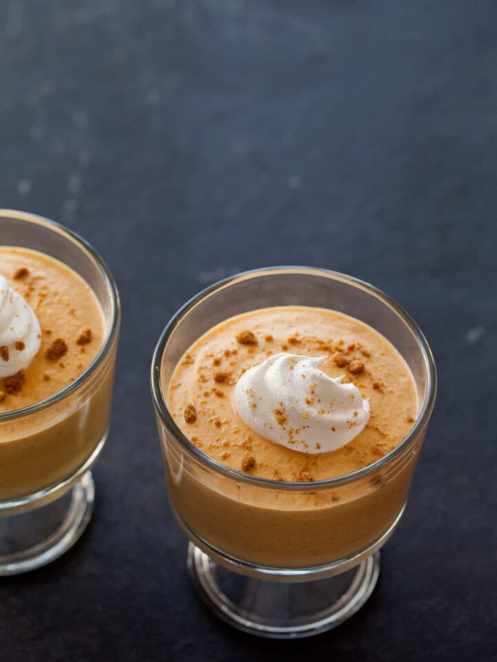 A close up of pumpkin mousse with a dollop of whipped cream and crumbled ginger snaps.