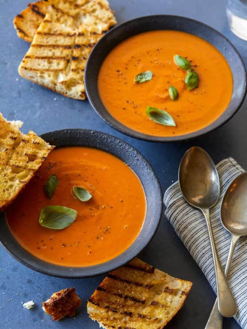 Two bowls of creamy roasted tomato basil soup with grilled bread, napkins, and spoons.