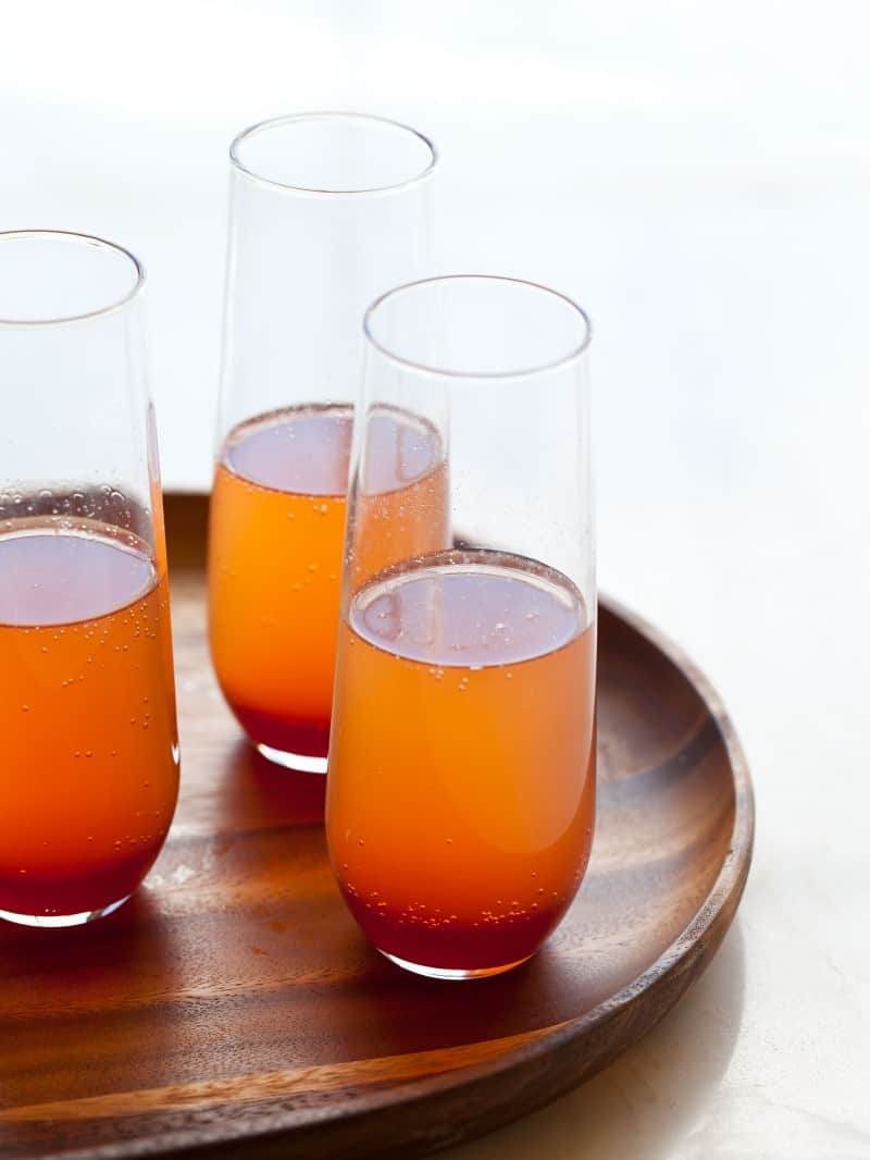 A glasses of spicy blood orange champagne punch on a wooden tray.