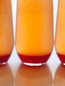 A close up of several spicy blood orange champagne punch in glasses.
