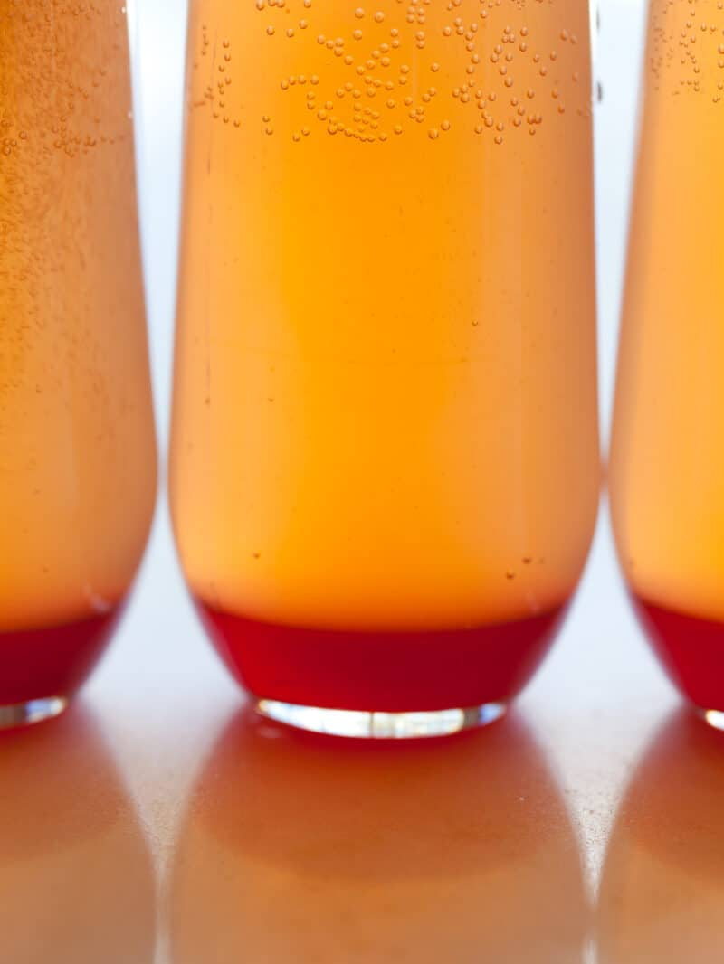 A close up of spicy blood orange champagne punch cocktails.