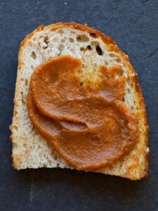 A close up of a piece of bread with sweet pumpkin butter spread on top.