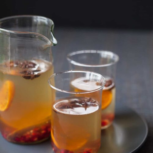 A recipe for Spiced White Wine Sangria with cinnamon sticks, star anise, and tangerines.