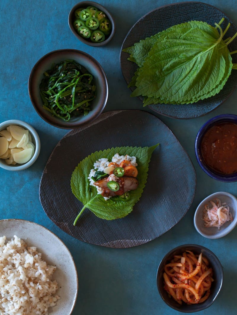 Ingredients in bowls and on plates and an assembled bo ssam bite.