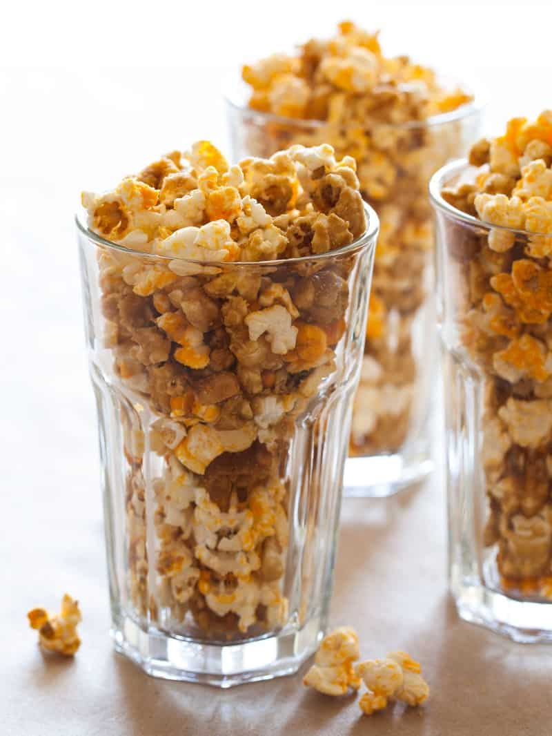 A close up of tall glasses full of cheddar and caramel popcorn mix.