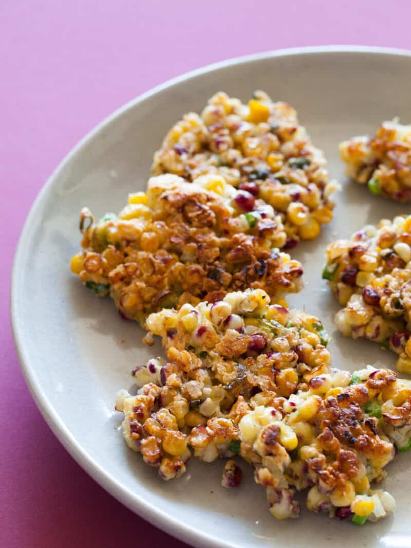 Crispy corn cakes stacked on one another on a plate.