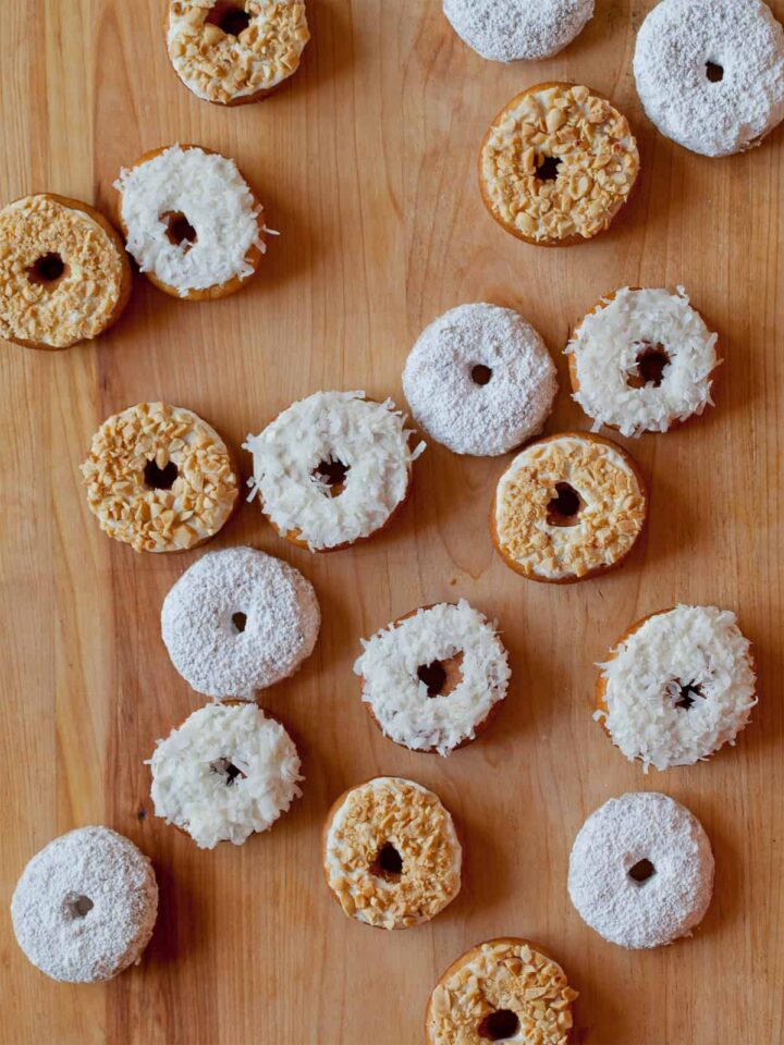 No yeast cake doughnuts with a variety of toppings on a wooden countertop.