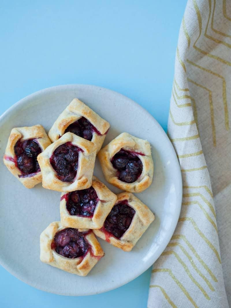 Mini blueberry galettes on a light blue plate with a printed napkin.