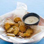 A plate of fried pickle chips and a small bowl of bleu cheese dipping sauce.