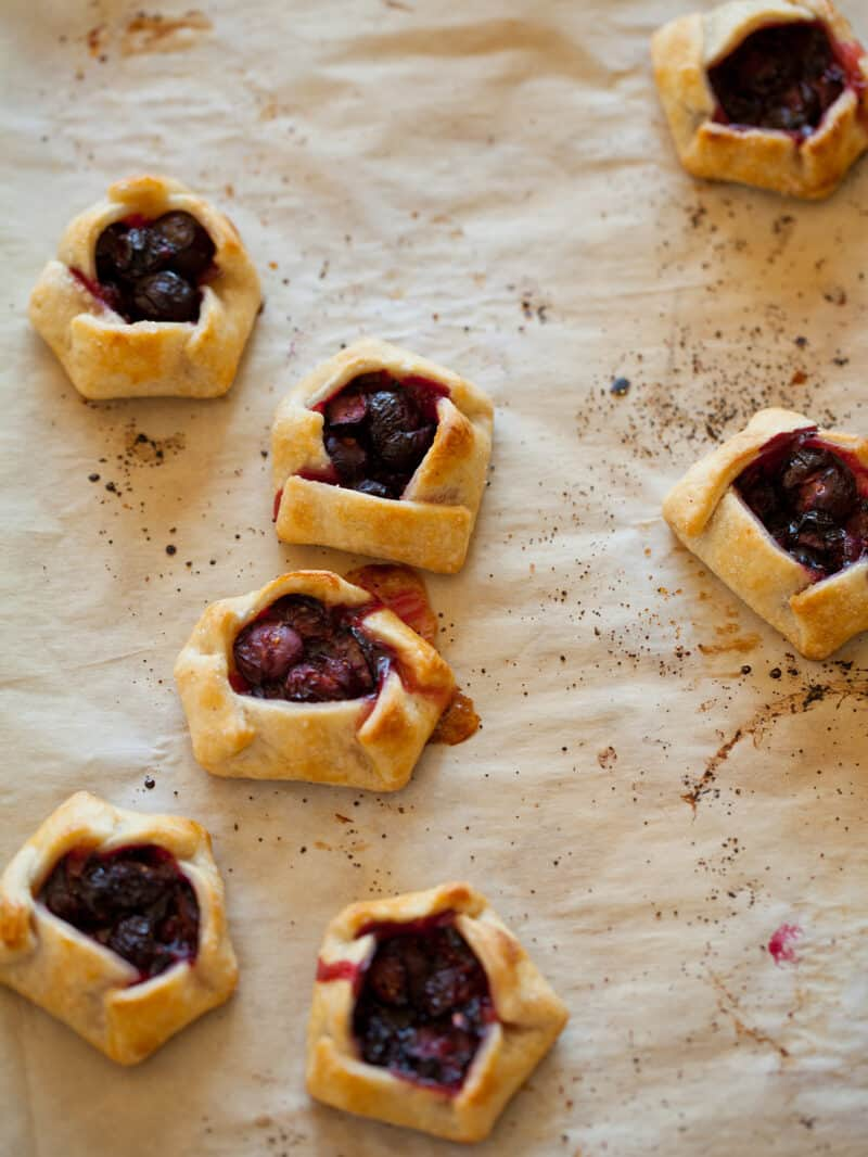 A close up of mini blueberry galettes on parchment paper.