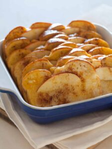 Baked apple french toast in a blue baking dish on a napkin.